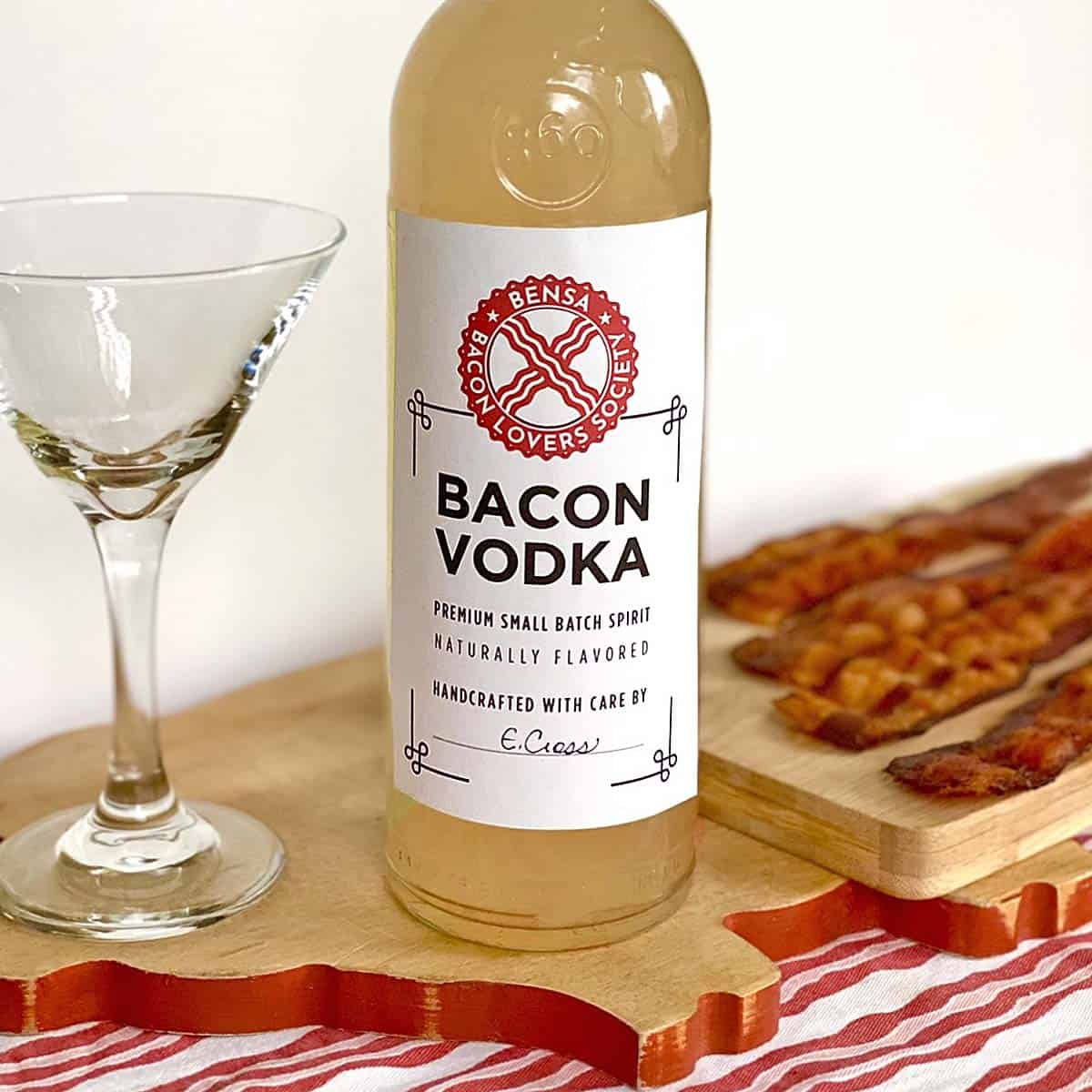 bottle of bacon vodka on a wooden cutting board, an empty martini glass, and four strips of crisply cooked bacon