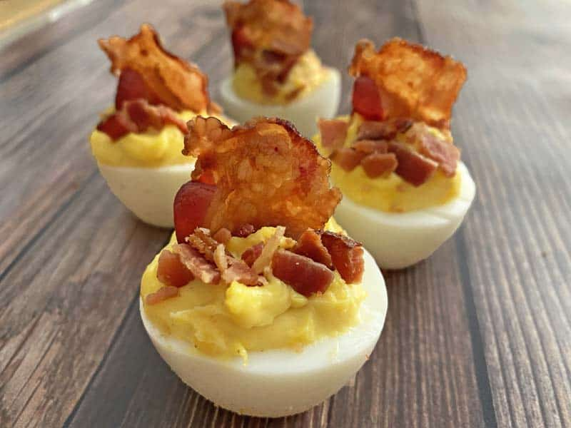 four deviled eggs garnished with bacon against a wooden background