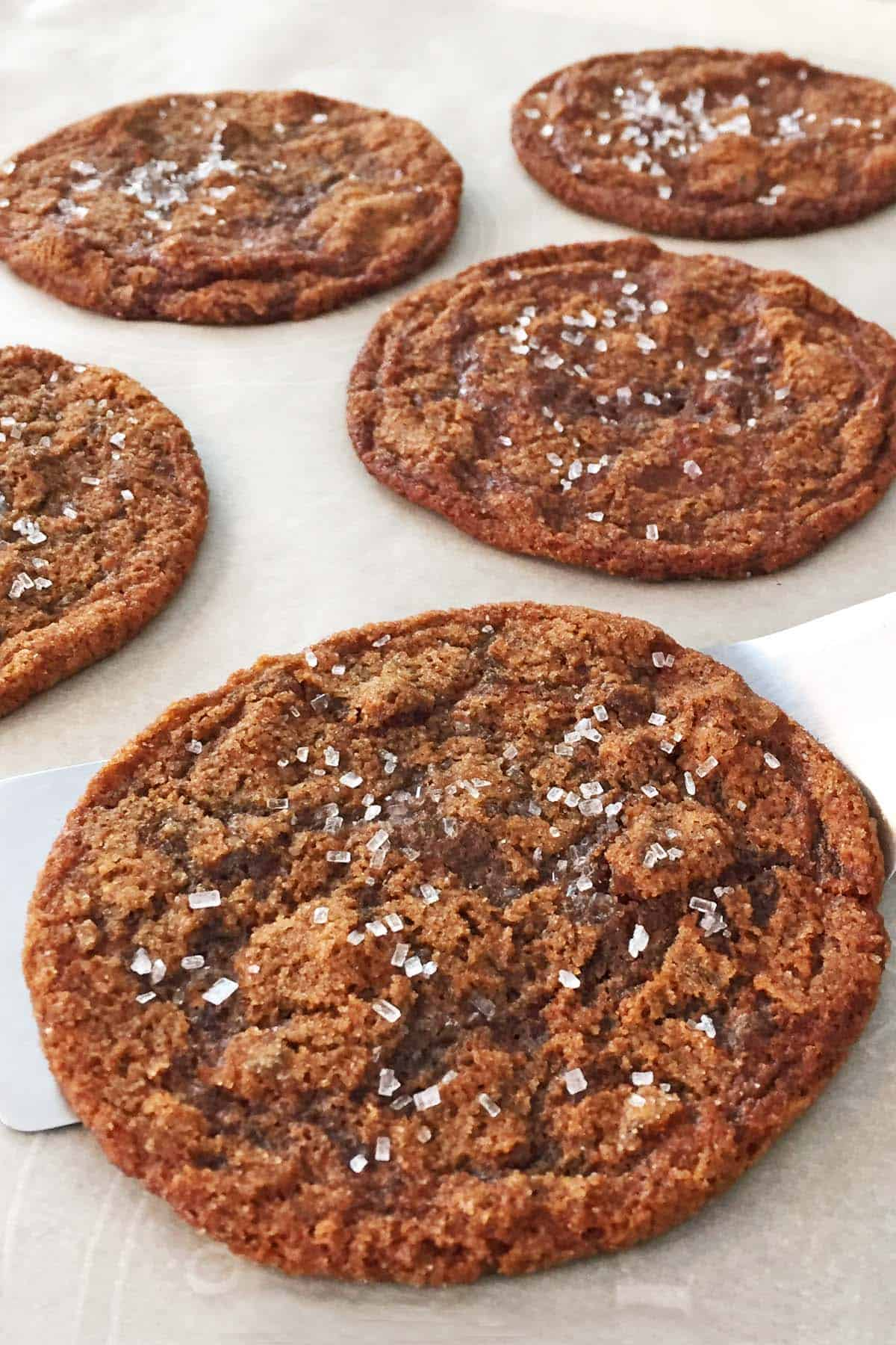 Five ginger bacon grease cookies on a parchment lined baking sheet