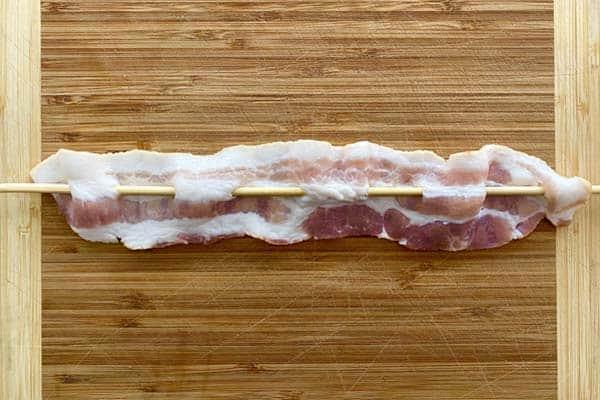 Bacon threaded on a skewer, resting on a cutting board