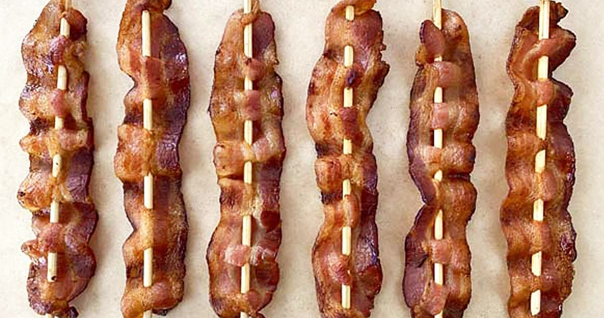 6 bacon skewers arranged on a tan parchment paper background.