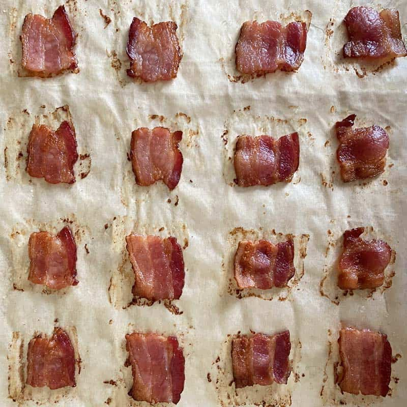 Golden brown crispy bacon squares hot from the oven on a parchment lined baking sheet.