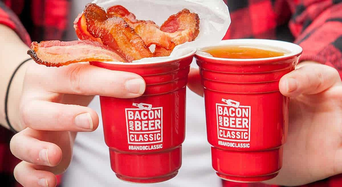 two hands holding red beer cups that say Bacon and Beer Classic