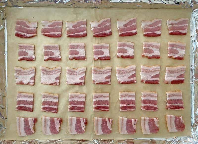 Squares of bacon arranged on a baking sheet lined with foil and parchment paper