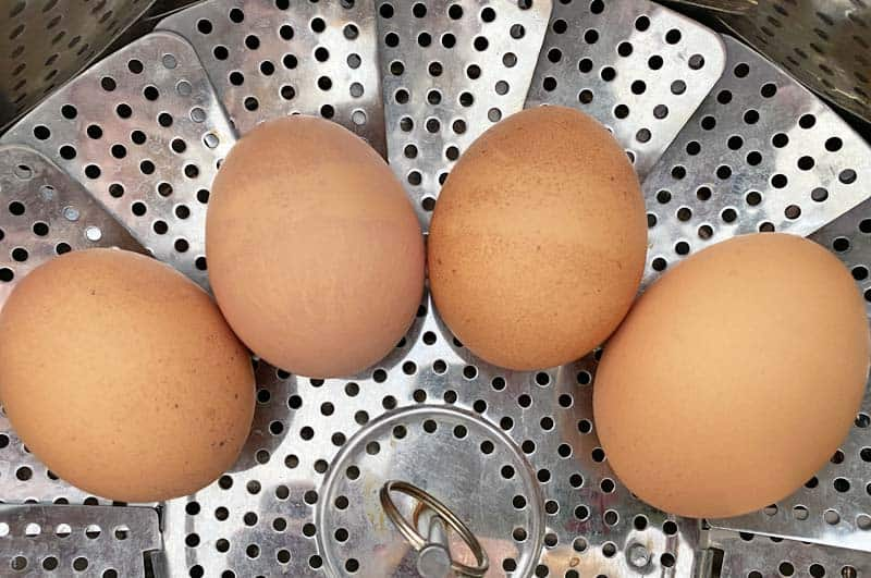 four eggs in a stainless steel steamer basket