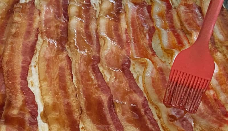 A red silicone brush shown glazing the bacon strips