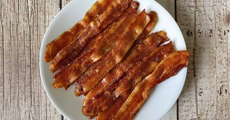 A white plate filled with maple candied bacon, set against a rustic white wooden background.