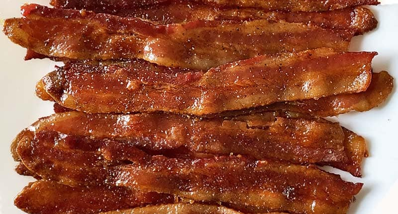 Twelve slices of maple candied bacon arranged in a pile.