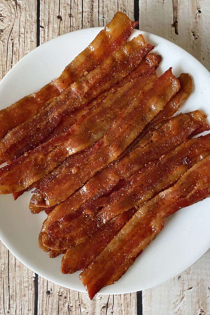 A dozen slices of finished maple candied bacon on a white plate.