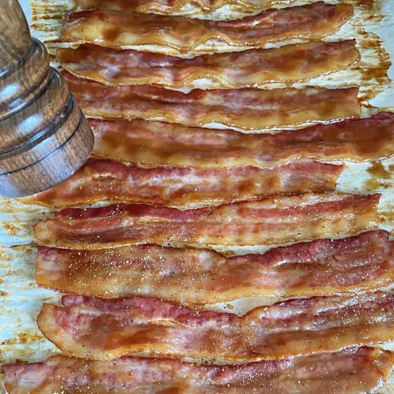 Partially cooked bacon strips on a baking sheet with a pepper grinder to the left.