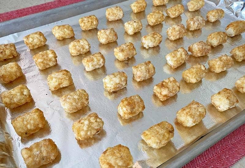 frozen tater tots arranged on a foil-lined baking sheet