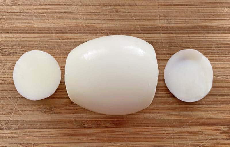 One hard boiled egg on a bamboo cutting board with two small pieces trimmed from the ends