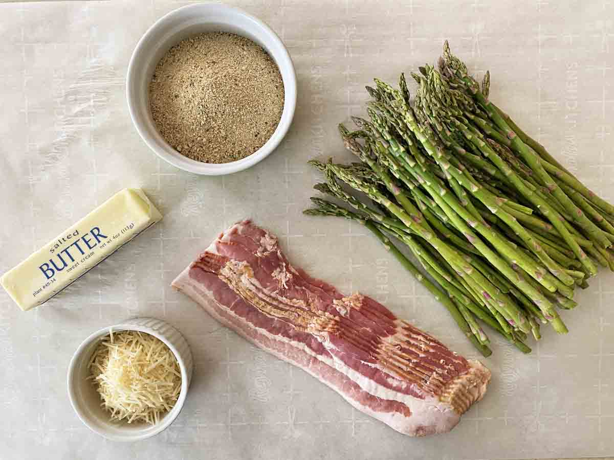 One and one half pounds of asparagus spears, a pound of bacon slices, a stick of butter, a bowl of Italian bread crumbs and a small bowl of shredded Parmesan cheese