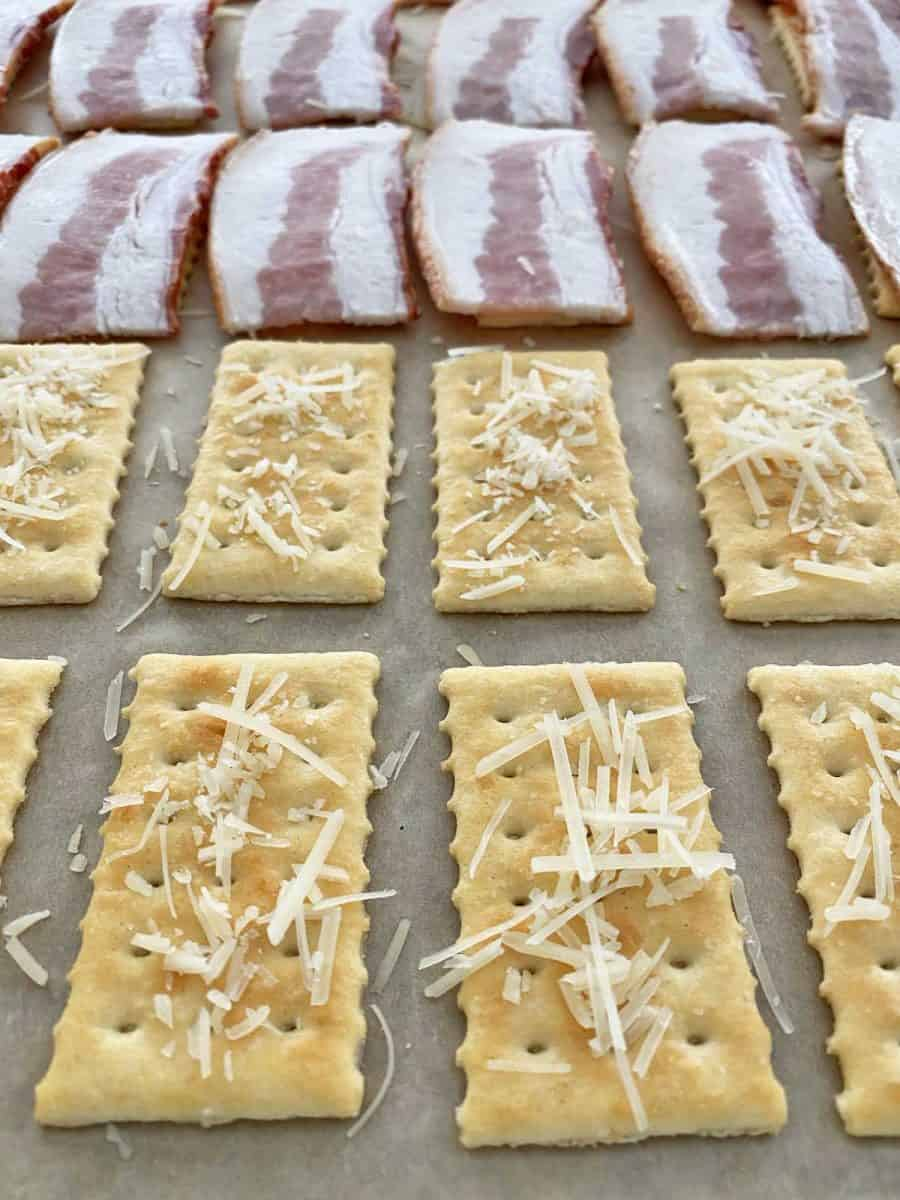 Close up of 16 club crackers sprinkled with Parmesan cheese and topped with bacon pieces.
