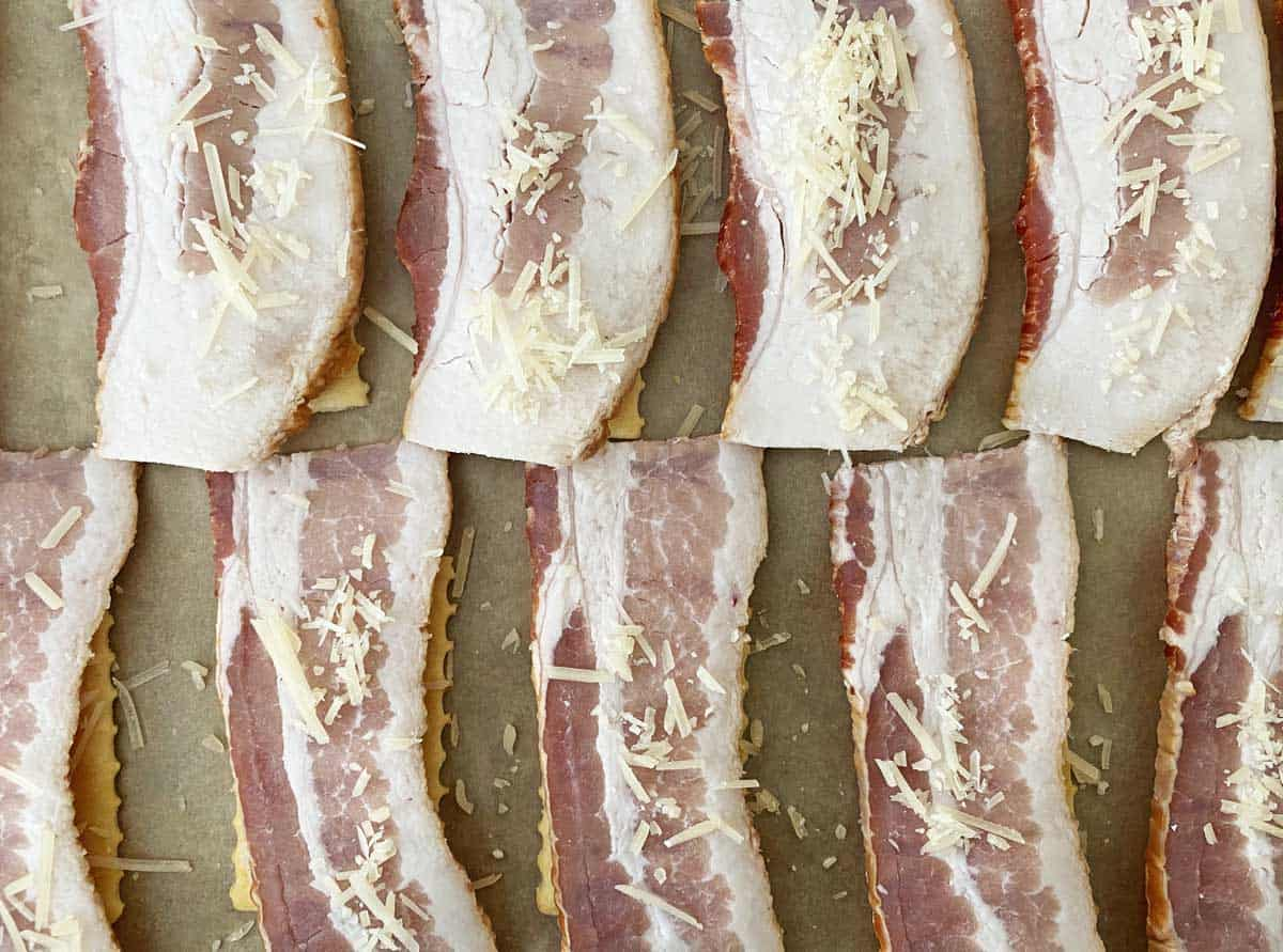 Uncooked bacon crackers sprinkled with parmesan on a parchment lined baking sheet