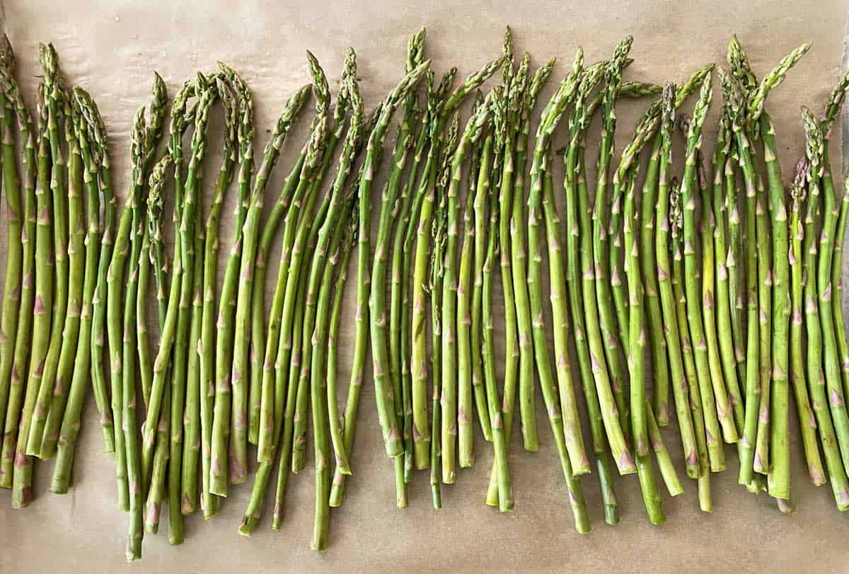 One and one half pounds of fresh asparagus spears spread in a single layer on a parchment lined baking sheet.