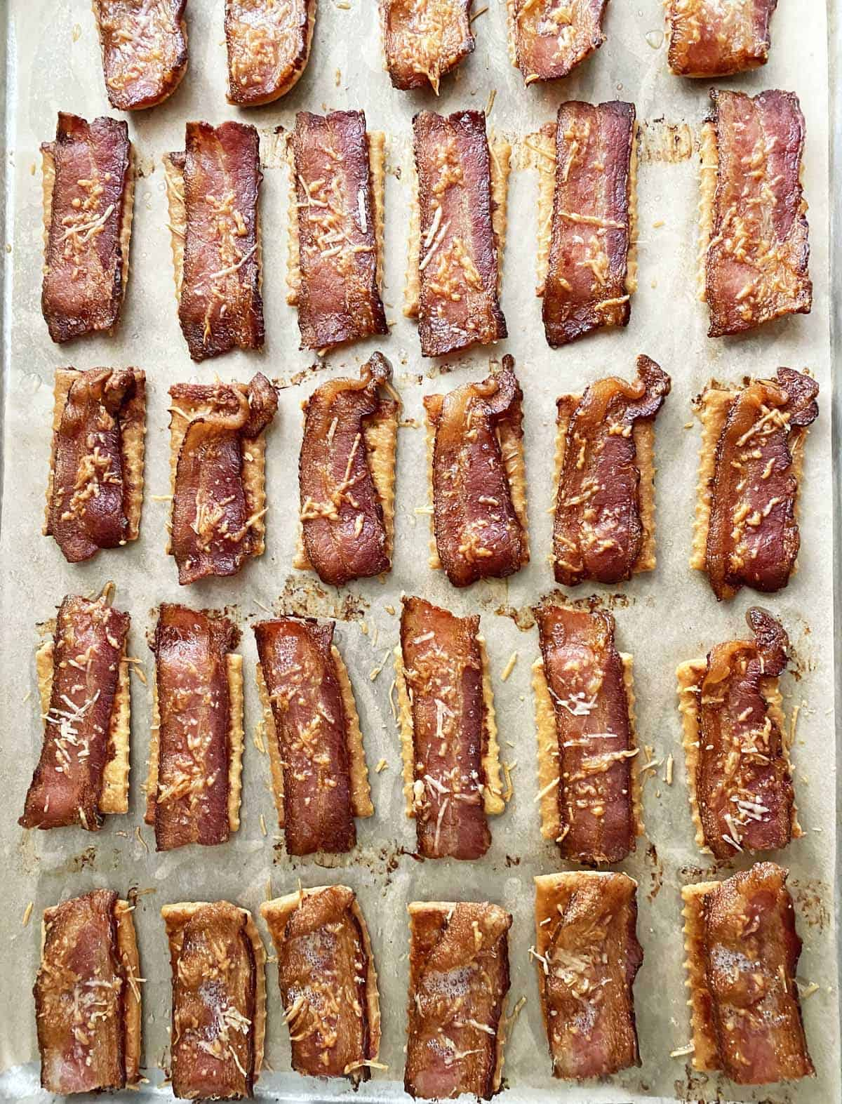 Cooked bacon crackers on a parchment paper lined baking sheet