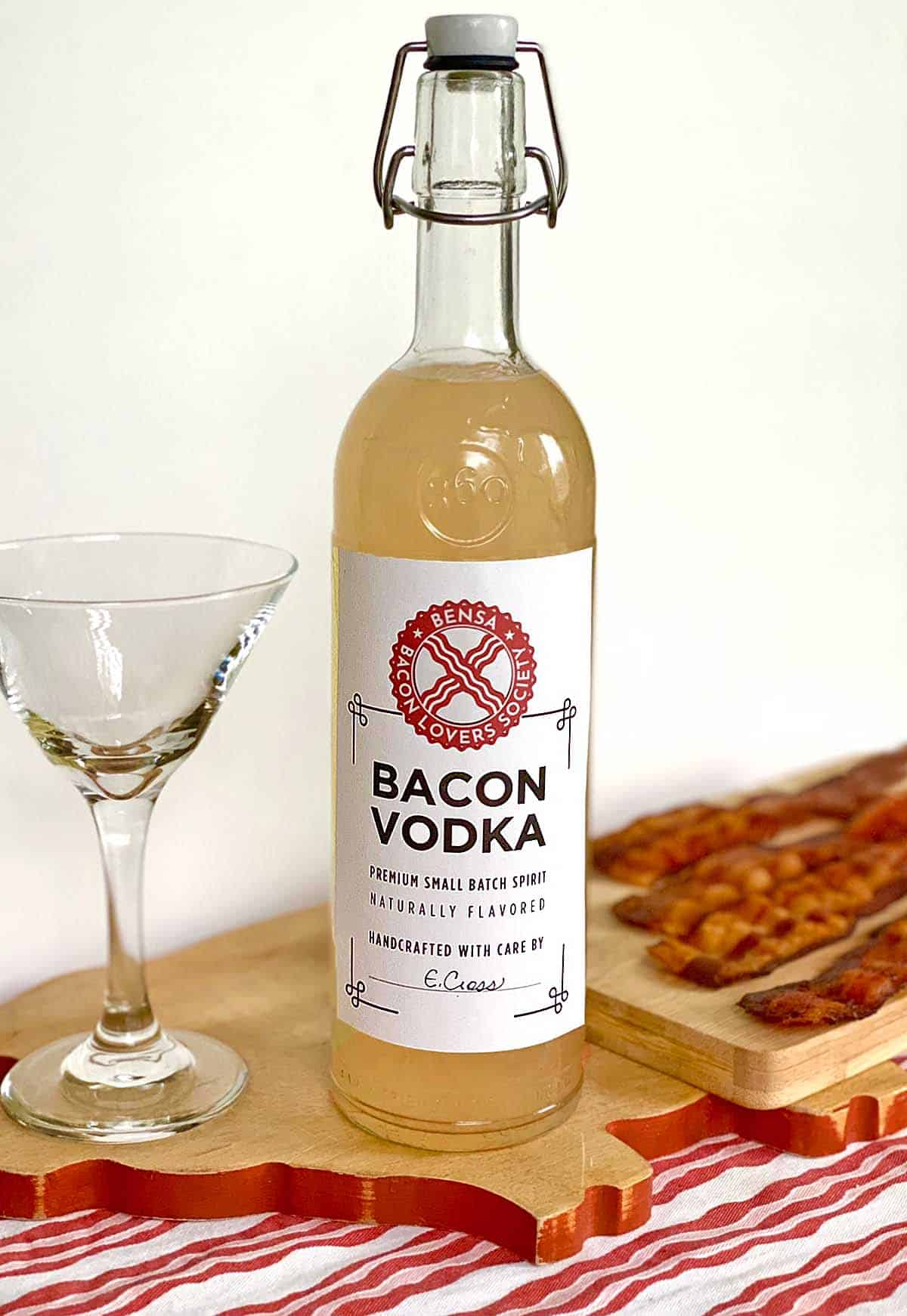 A close up of a bottle of bacon flavored vodka with a cocktail glass on the left and four slices of cooked bacon in the background.