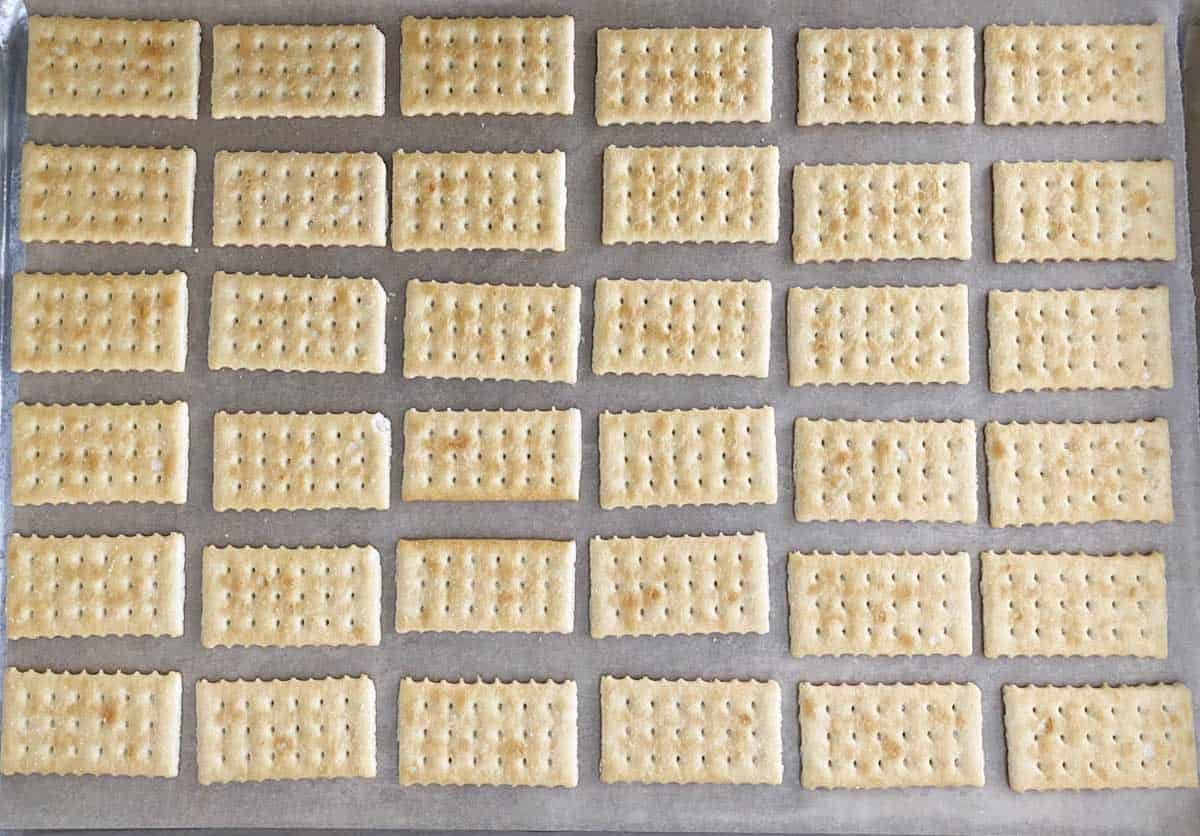 30 club crackers arranged in rows on a baking sheet lined with parchment paper.