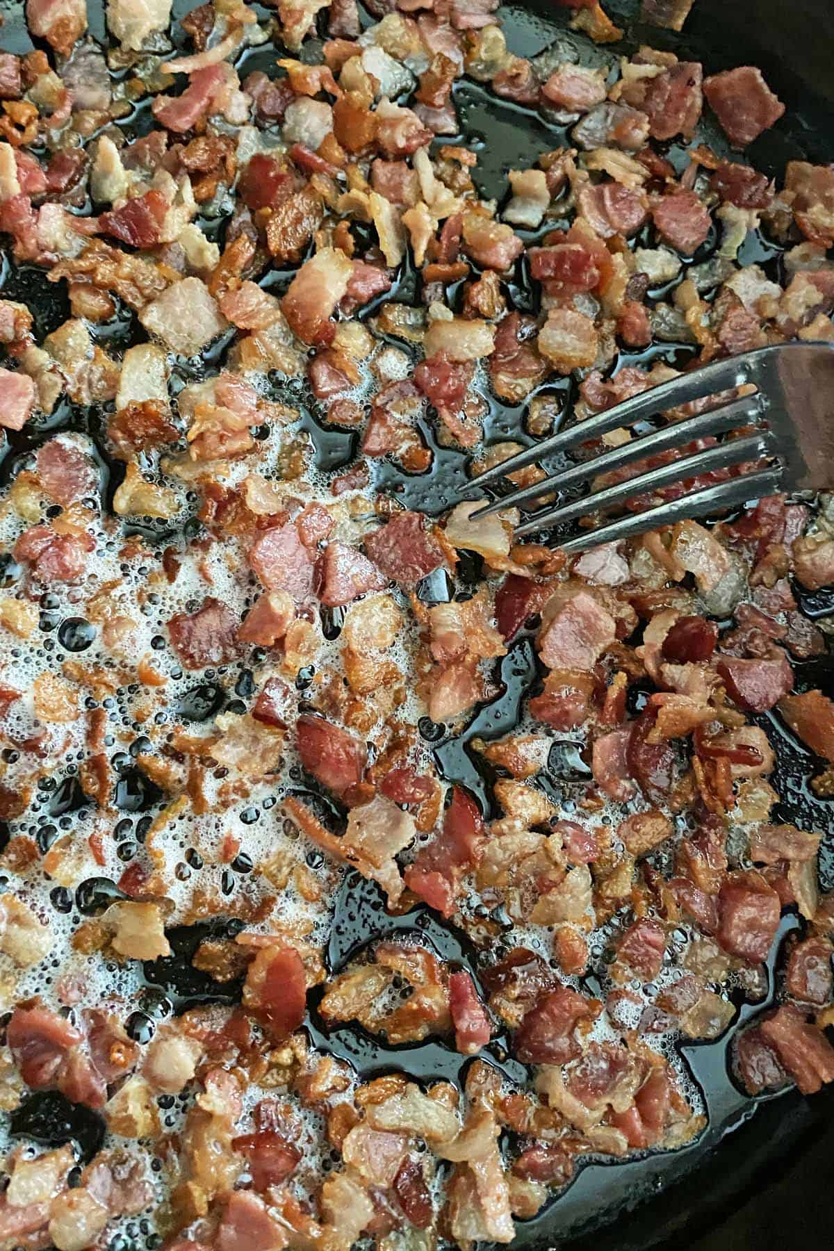Chopped bacon frying in a large skillet. The bacon bits are browned and almost done cooking.