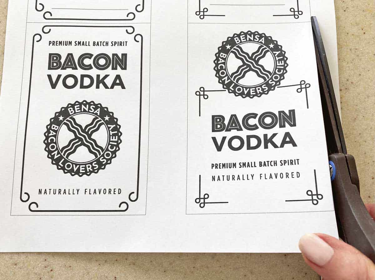 A hand shown with a pair of scissors, cutting a sheet of bacon vodka labels