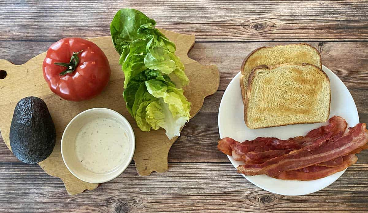 A ripe avocado, a medium tomato, four butter lettuce leaves, ranch balsamic sauce, two pieces of toast and four pieces of bacon,