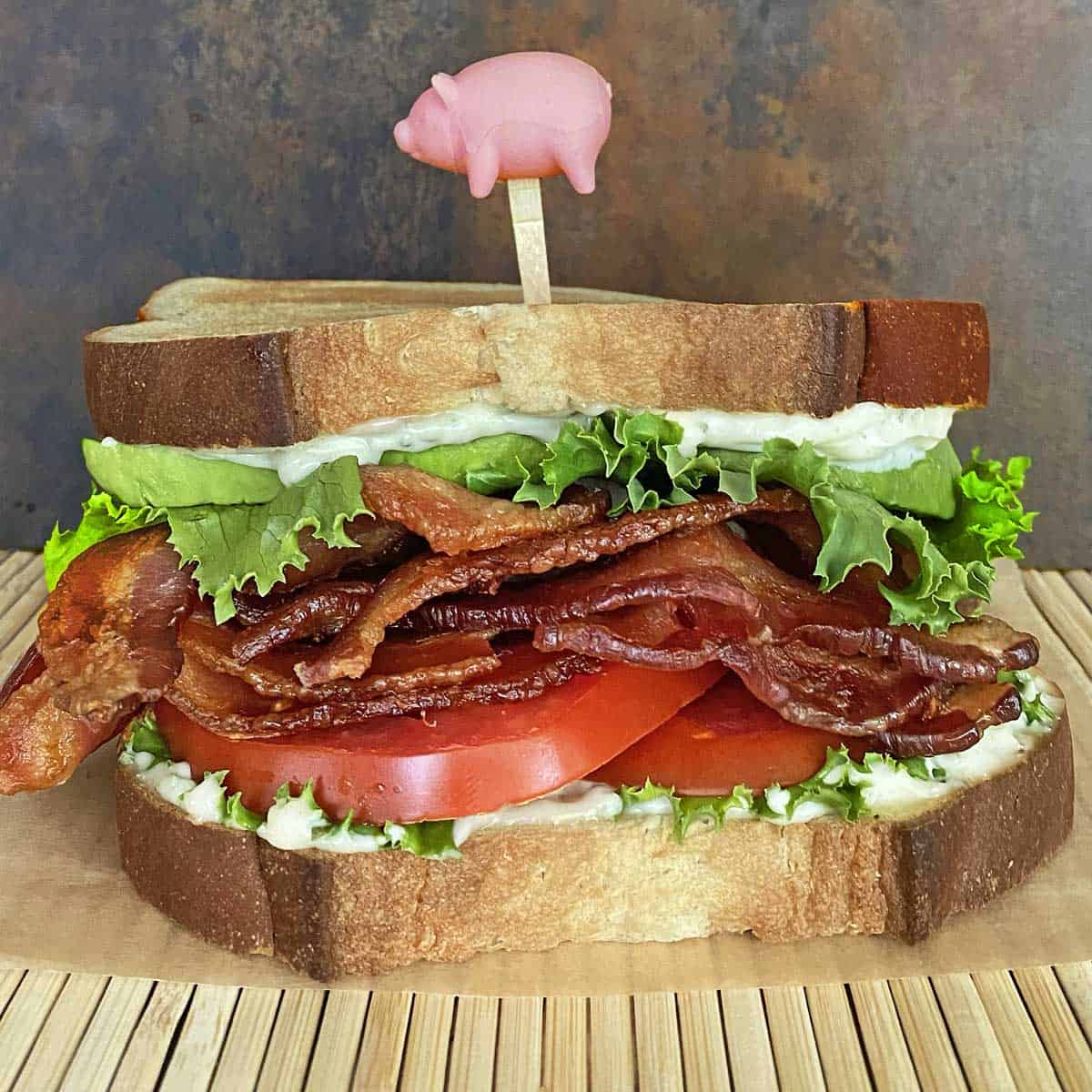 bacon lettuce avocado tomato sandwich skewered with pig toothpick