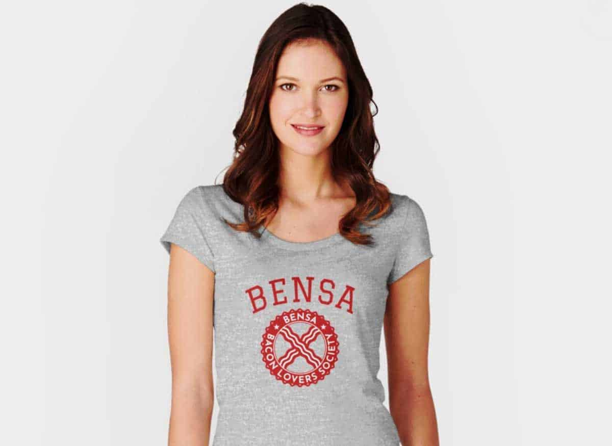 A young woman wearing a gray tshirt imprinted with BENSA and BENSA Bacon Lovers Society logo