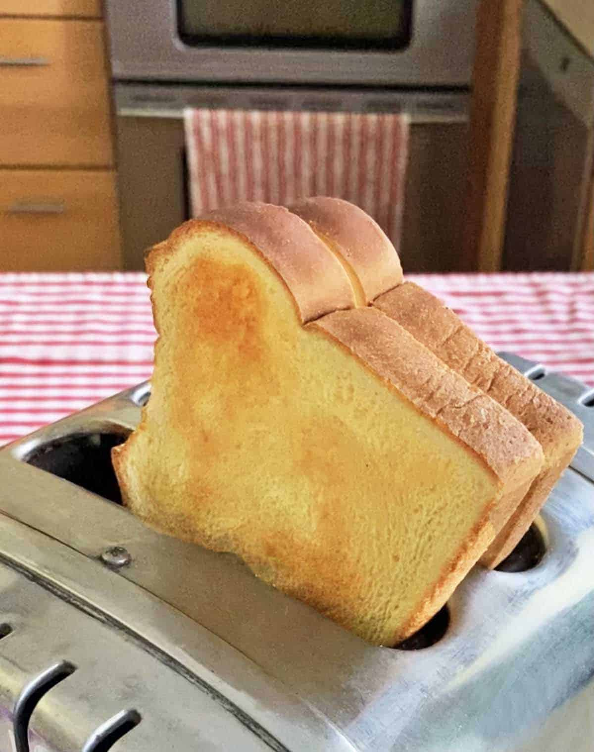 Two pieces of toasted bread popping out of a toaster in a kitchen.