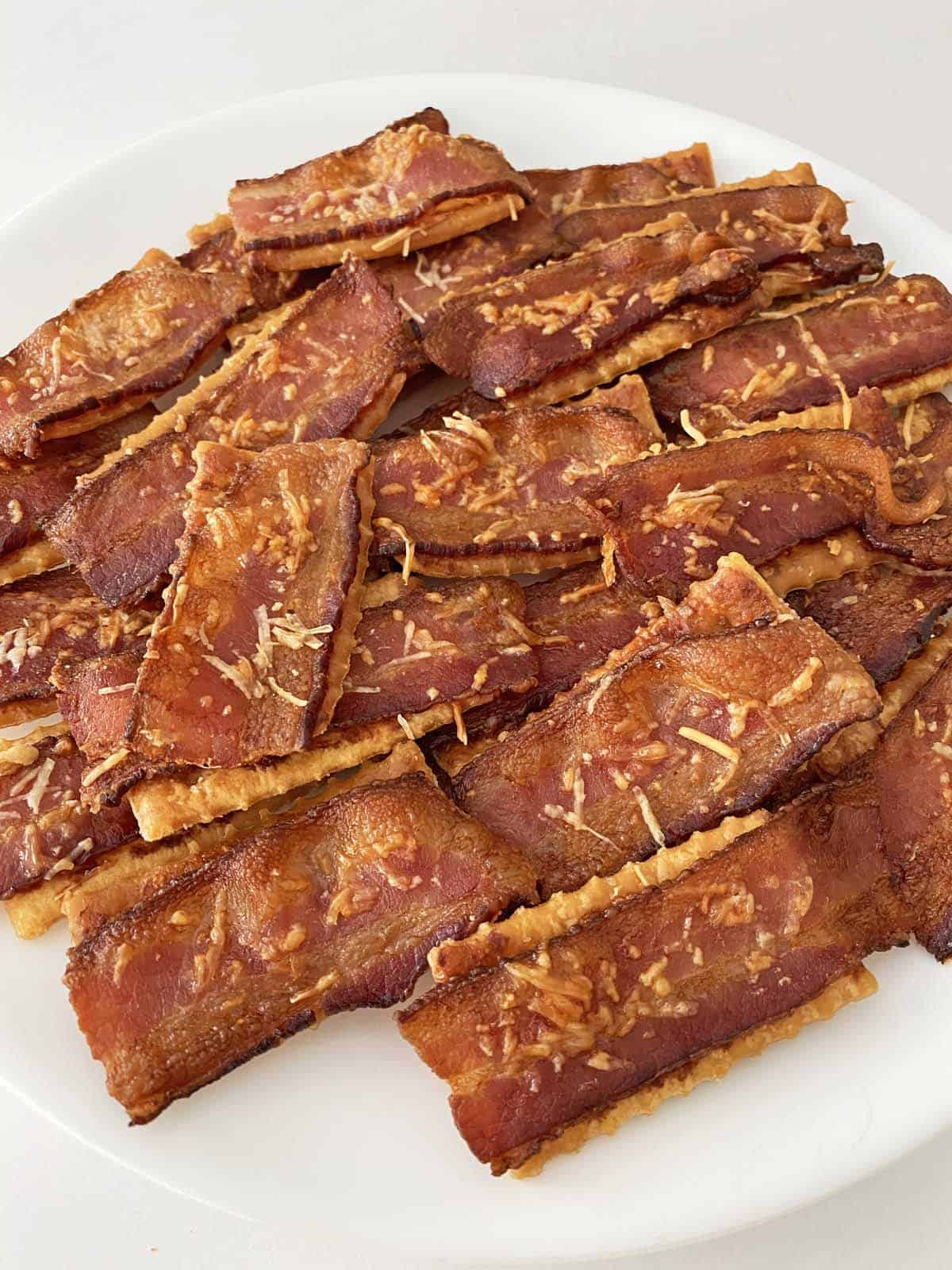 Bacon crackers baked with Parmesan cheese piled on a white plate.