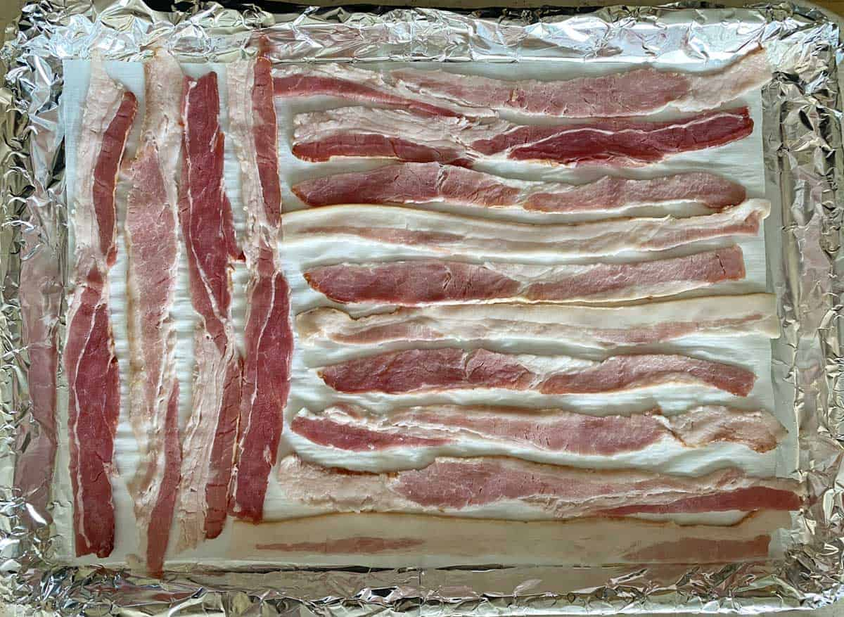 Uncooked bacon on a foil and parchment paper lined baking sheet
