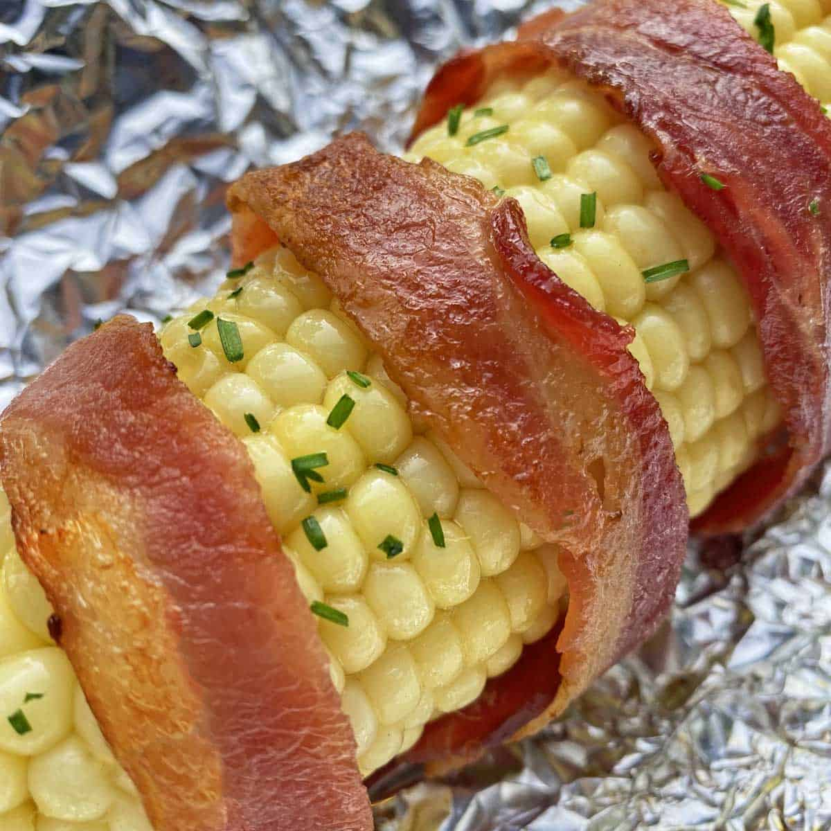 Close up of bacon wrapped corn on foil