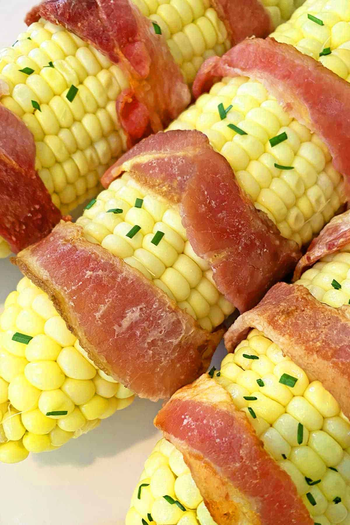 Three ears of fresh sweet corn on the cob wrapped in bacon