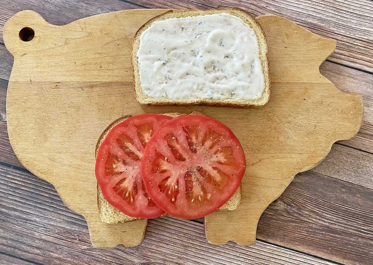 Cutting board with two pieces of toast topped with mayo and tomato slices