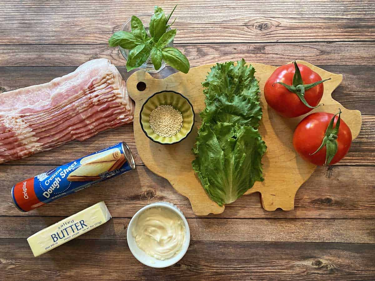 Bacon, fresh basil, sesame seeds, lettuce, two tomatoes, mayonnaise, butter and a tube of crescent dough sheets.