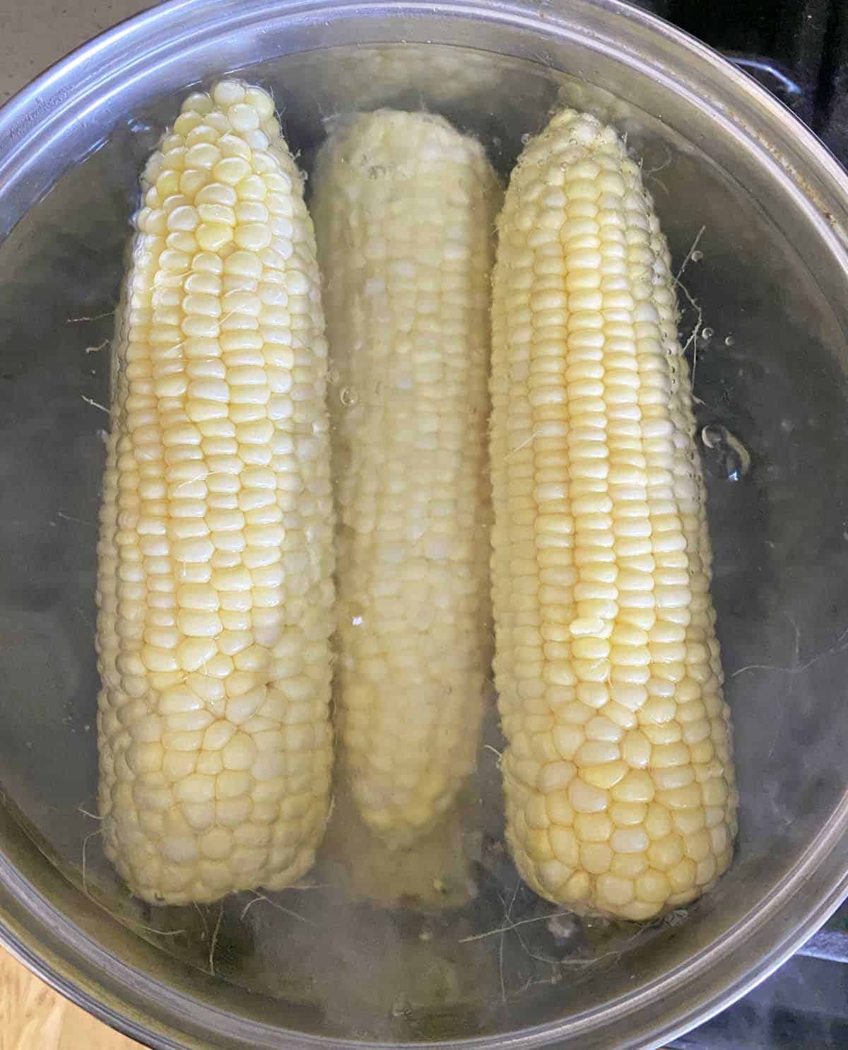 Six ears of corn cooking in a large pot of boiling water