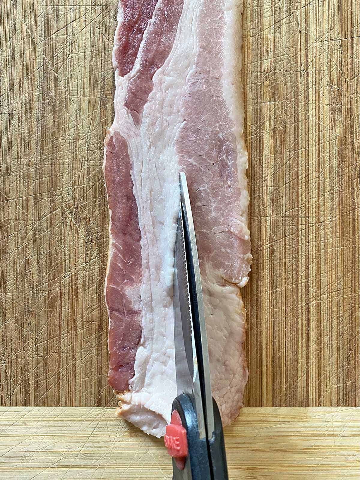 Scissors cutting a piece of bacon lengthwise in a strip