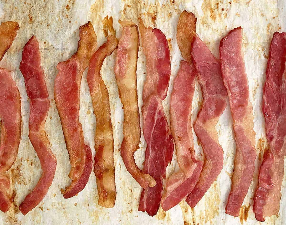 Partially cooked bacon on a parchment and foil lined baking sheet