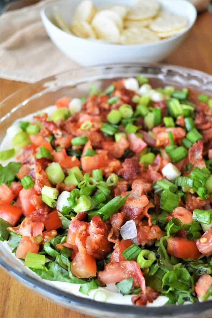 close up of BLT dip with crackers in the background