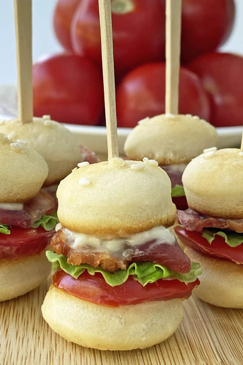 Close up of mini BLT sliders on toothpicks on a wooden cutting board with a bowl of tomatoes in the background.
