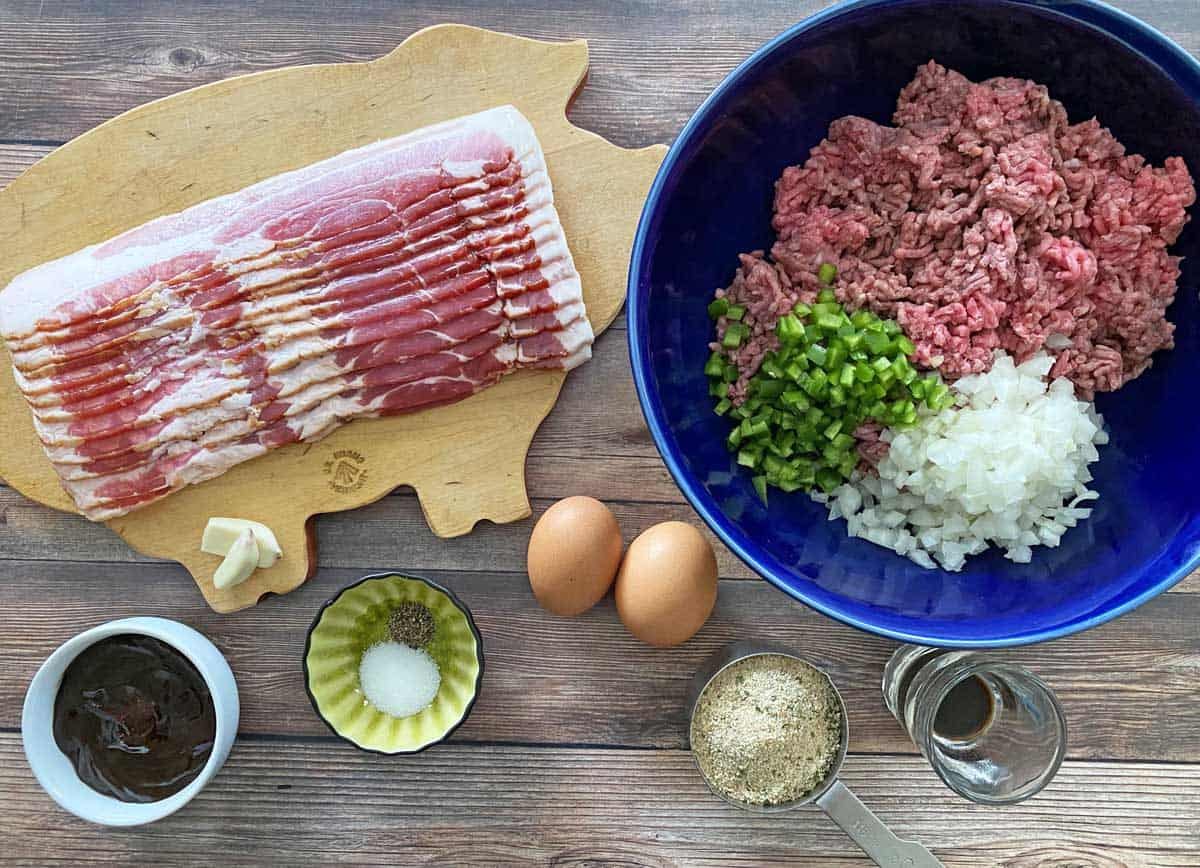 Bacon meatloaf ingredients including bacon, garlic cloves, BBQ sauce, 2 eggs, salt, pepper, bread crumbs, ground beef, chopped pepper and chopped onion.