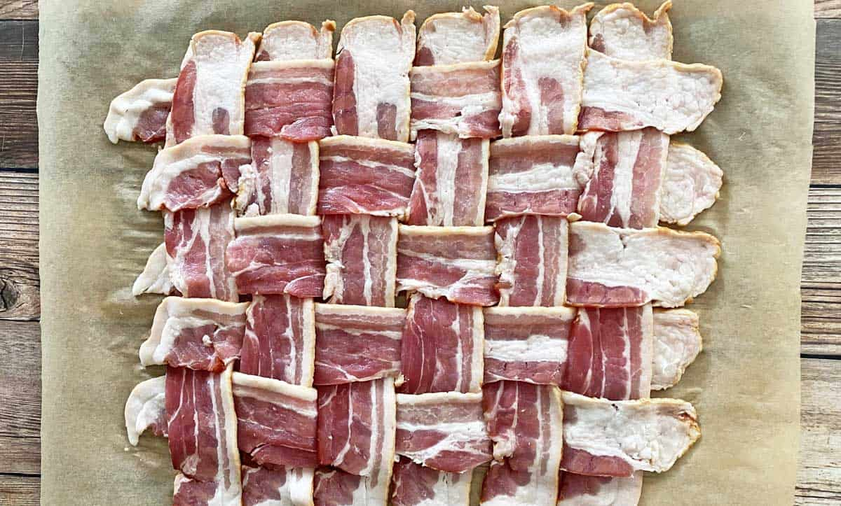 12 strips of bacon woven in a square, on a sheet of parchment paper