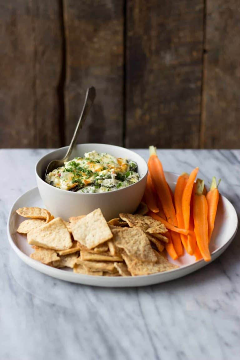 Cheesy spinach artichoke horseradish dip on a plate with crackers and veggies