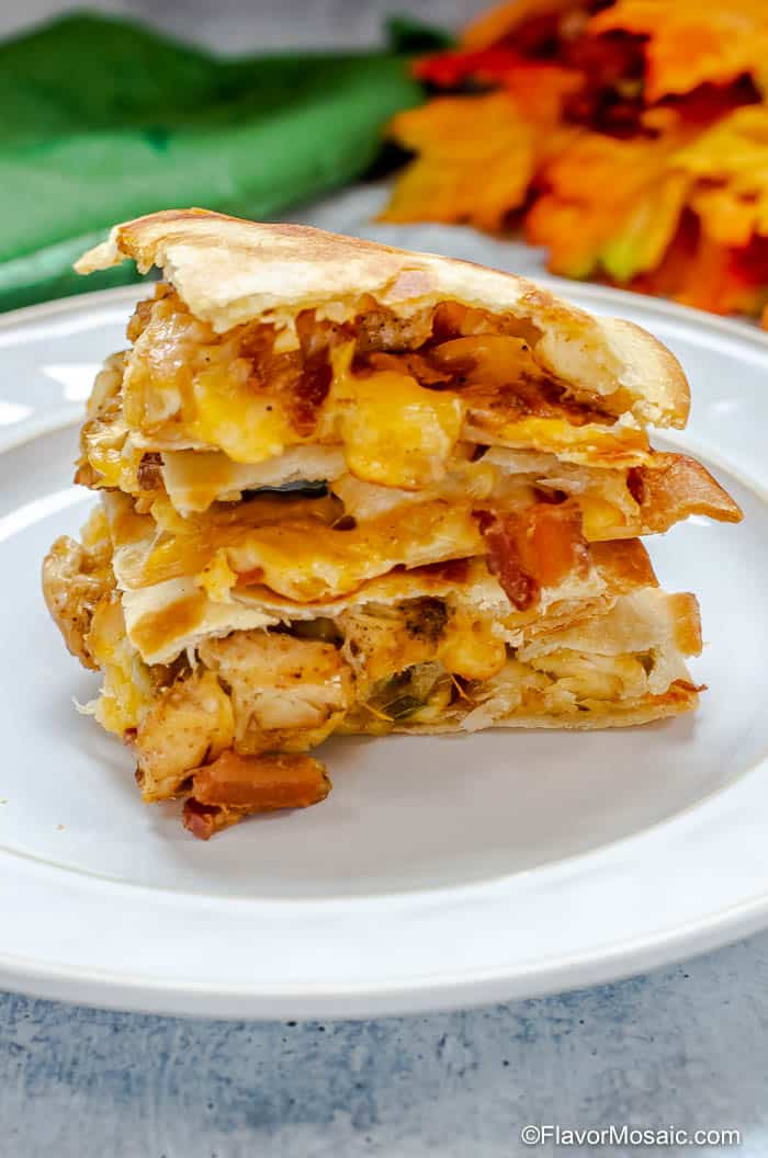 A stack of four chicken bacon ranch quesadillas on a white plate
