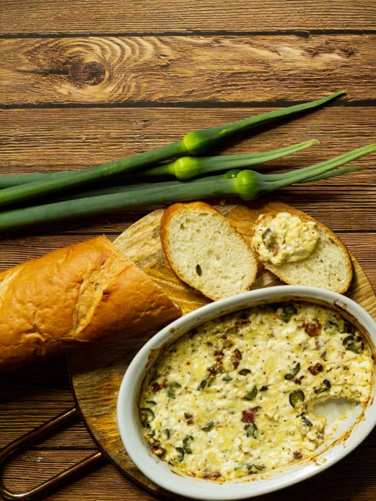 Leek scape bacon dip, a loaf of french bread, and three leek scapes