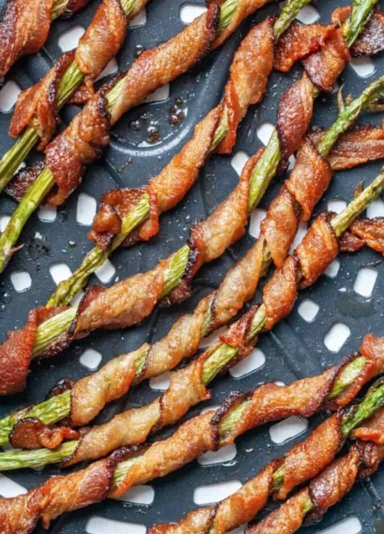 12 pieces of bacon wrapped asparagus inside an air fryer basket