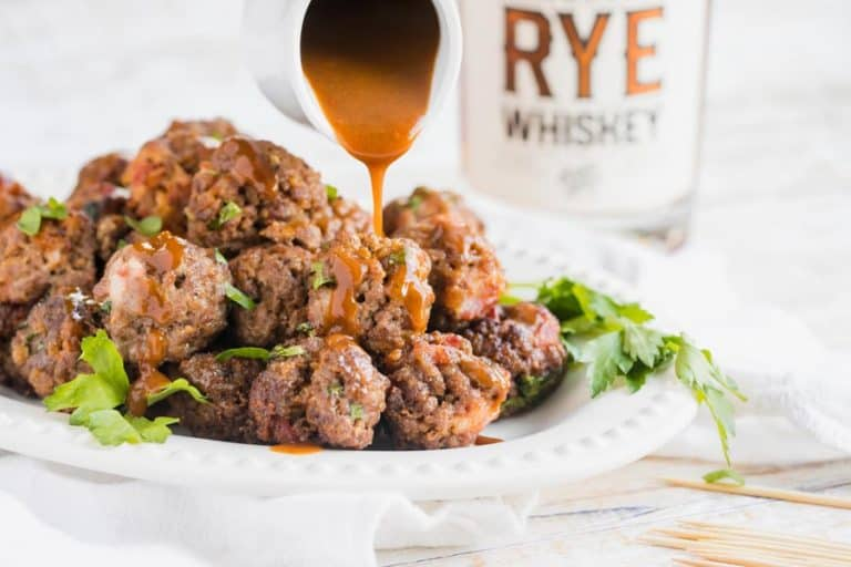 a platter of bacon bourbon meatballs with a small pitcher drizzling sauce over