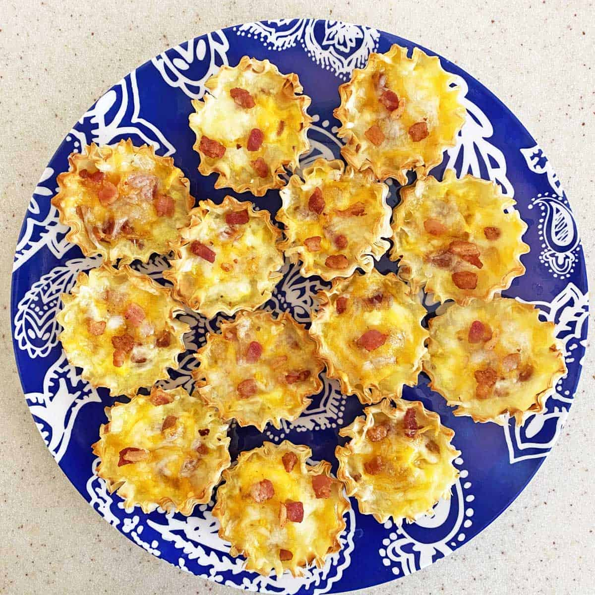 13 baby quiches with cheese and bacon on a blue paisley design plate.