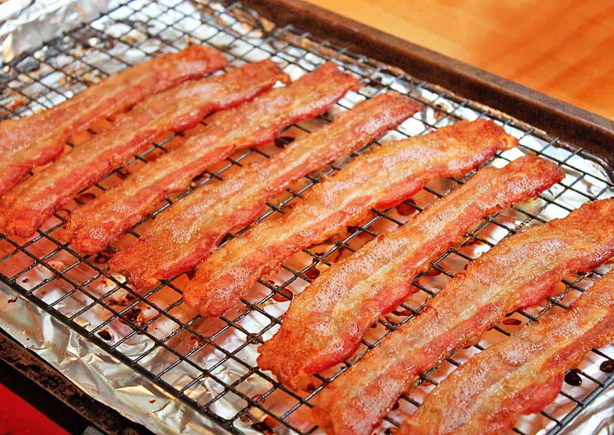 8 strips of crispy bacon on a bacon oven rack set over a foil-lined baking sheet.