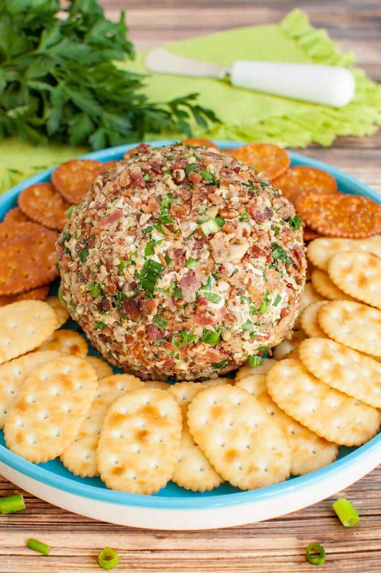 A bacon ranch cheese ball on a blue plate, surrounded by assorted crackers